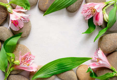 Spa background with sea stones and flowers