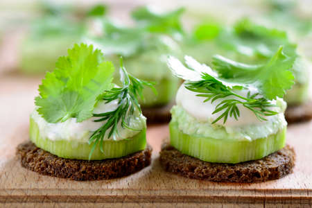 healthy snack: Cucumber and whipped with spring herbs feta cheese mini snacks seasoned with cilantro and dill Stock Photo