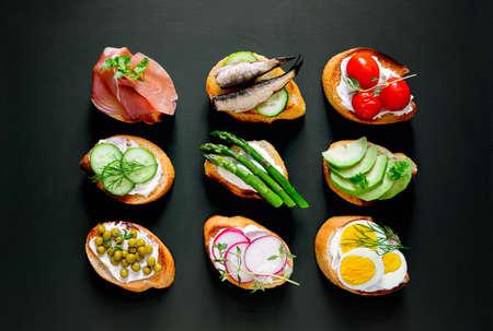Sanduíches em um fundo escuro, ou canapés variados, vista superior