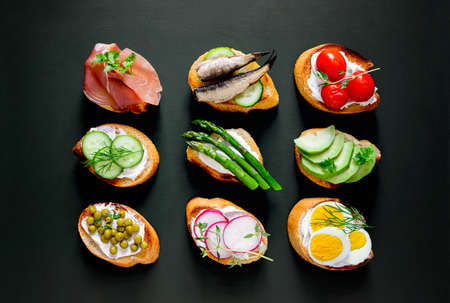 Sandwiches on a dark background, or assorted canapes, top view Фото со стока