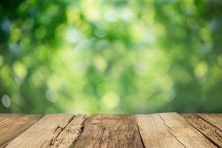 portada: Resistido rústico superficie de la mesa delante de fondo borrosa jardín Foto de archivo