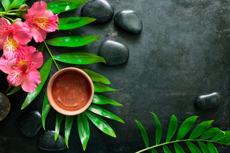 Dark spa summer background decorated wit palm leaves
