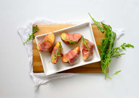 collation: Peach slices wrapped in prosciuto decorated with arugula fresh leaves, fast and simple party snack, top view