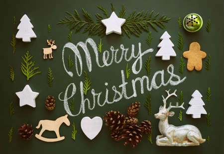 Merry Christmas greeting text on a chalkboard decorated with various Christmas staff, flat lay, view  from above, stylized photo Stock Photo