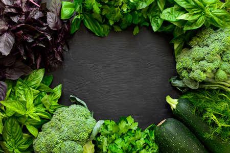 Green fresh vegetables on a black board, organic farm, or local farming or farm market concept, space for a text Stock Photo