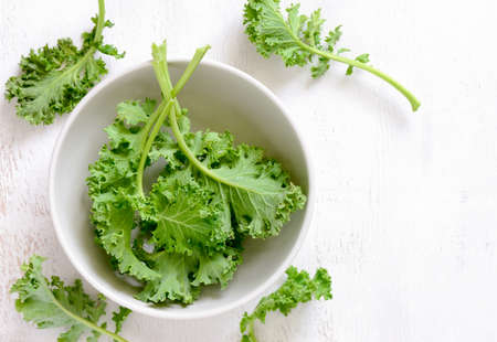 Kale leaves in a white bowl, view from above