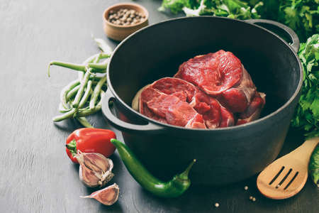 cast iron pan: Beef in a cast iron pan, cooking ingredients, meat and season vegetables, stylized photo