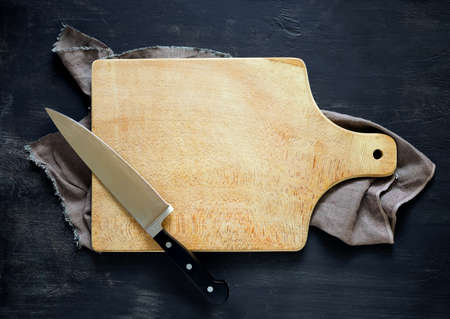 shef: Cooking concept, dark moody rustic kitchen background with an empty cutting board and Knife on it, space for a text, view from above