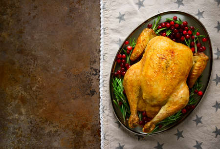 お祝いの伝統的な食べ物、楕円形の皿に鶏のロースト ローズマリーとクランベリーで飾られ、挨拶や本文、上からの眺めを招いてのスペースがあり