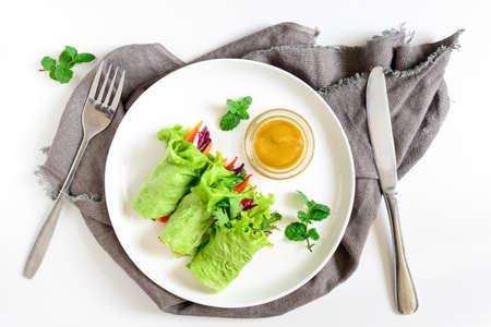 レタスのベジタリアン ラップまたはみじん切りたてのジューシーな野菜詰めロールし、添え、新鮮なミントの葉で飾られた、ハーブを上から表示
