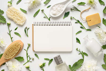 Spa floral background, flat lay of various beauty care products decorated with simple white flowers, paper note with a blank space for your text