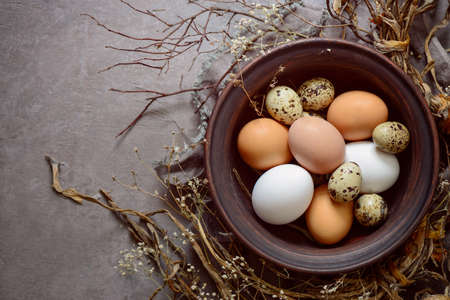 laying egg: Easter composition with various natural coloured eggs in a rustic plate, moody warm grey and brown palette, view from above