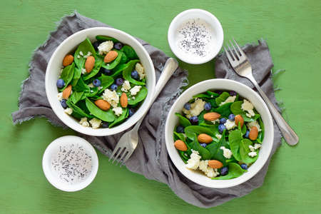 breackfast: Spinach, almond and goat cheese salad served in bowls with yogurt and poppy seed dressing in two cups, view from above
