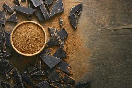 Dark chocolate pieces crushed and cocoa powder in wooden bowl on a dark surface, view from above, space for a text
