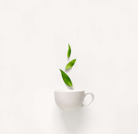 Cup of fresh green tea with green leaves rising above, tea aromatic qualities concept