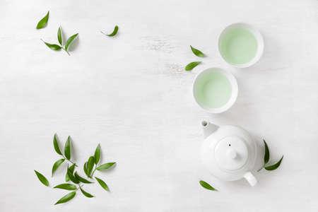 紅茶とティーポットの茶葉、上からの眺め、テキストのためのスペースで囲まれた 2 つの白いカップ ティー コンセプト