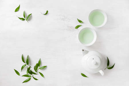 Tea concept, two white cups of tea and teapot surrounded with green tea leaves, view from above, space for a text 版權商用圖片 - 73370365