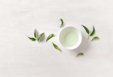 Tea concept, white cup with tea surrounded with green tea leaves, view from above