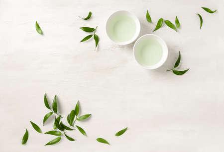 Concept de thé, deux tasses de thé blanc entourées de feuilles de thé vert, vue de dessus, espace pour un texte