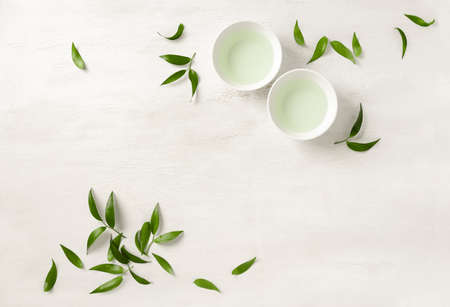 Tea concept, two white cups of tea surrounded with green tea leaves, view from above, spacefor a text