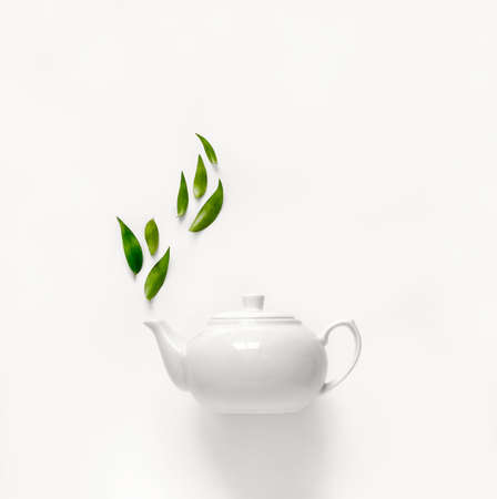 Teapot of fresh green tea with green leaves rising above, tea aromatic qualities concept