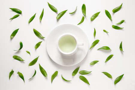 녹색 잎 주위에 신선한 녹차의 컵, 위에서 볼