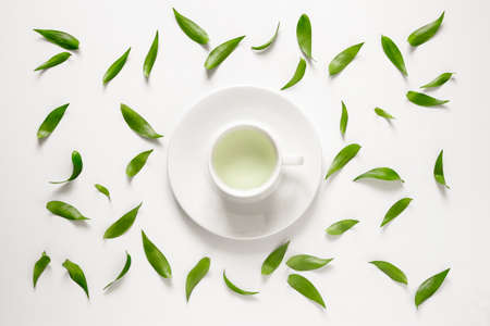 Cup of fresh green tea with green leaves around it, view from above Foto de archivo