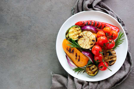 Various grilled vegetables in a plate, view from above, space for a text