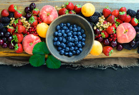 Various summer garden berries background with a space for a text, view from above, flat lay Imagens