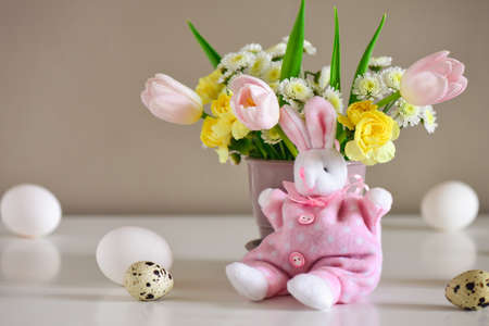 Easter greeting concept, spring flowers bouquet on a plain table surface  decorated with various kinds of Easter natural colored eggs, with a cute pink bunny sitting in front of vase with flowers