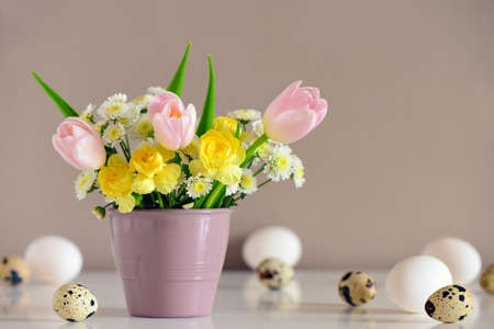 Easter greeting concept, pastel colored bouquet on a table surface covered with various kinds of natural Easter eggs, space for a text, front view