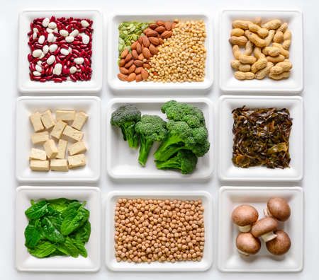 Set of various vegan protein sources, assortment of vegan protein rich alimentary products such as tofu, legumes, nuts, seaweeds and other, view from above, flat lay Stock Photo