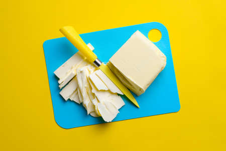 Butter diced with yellow knife, minimal butter concept, view from above