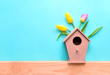 Spring concept background with birdhouse decorated with tulips, composition with a space for a text