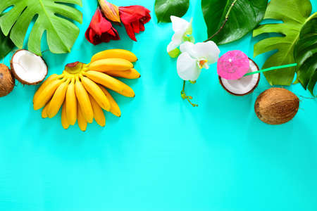 Summer tropical background with fruits and tropical flowers and leaves, overhead view, space for a text Stock Photo