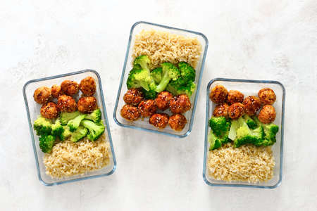 Asian style teriyaki sauce chicken meat balls with broccoli and rice prepared and put in a take away lunch boxes, view from above