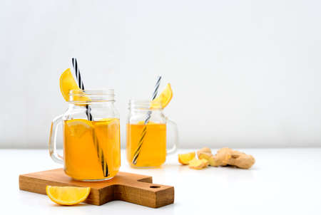 Ginger and lemon combucha detox drink in two jars with straws, front view, space for a text