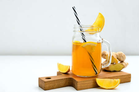 Ginger and lemon combucha detox drink in a jar with a straw, front view, space for a text Stock Photo