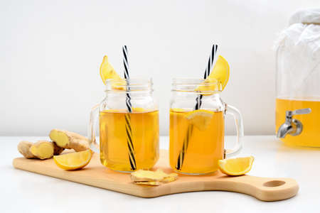 Ginger and lemon combucha detox drink in two jars with straws, front view Stock Photo