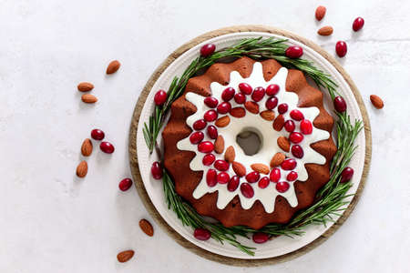 Christmas festive pound cake decorated with cranberries almonds and rosemary twigs, view from above