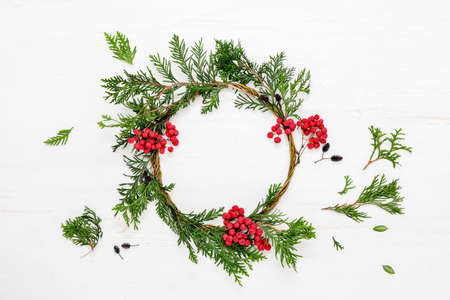 Noel or Christmas background with handmade Xmas wreath decorated with red berries, view from above, space for a text