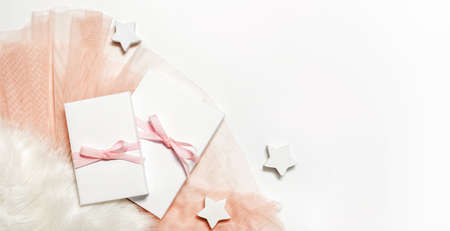 Festive Christmas feminine gift concept with presents packed in white paper lying on white faux fur and pink fabric, view from above