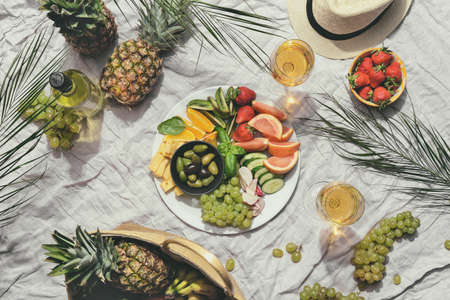 Summer beach picnic table setting concept, view from above on fruit snaks and wine served on a linen beach rug Archivio Fotografico