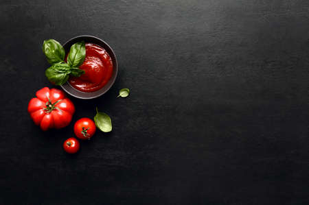 Tomato sauce or ketchup culinary concept, dark food background with blank space for a text, top down view Stock Photo