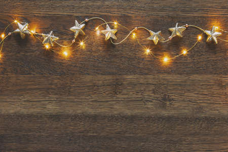 Christmas garland with golden stars lying down on wooden background lighten up by decorative lights, view from above, space for a greeting text