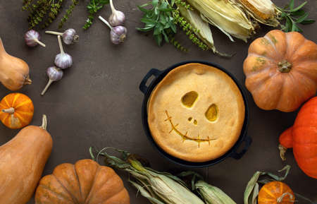 Halloween kids party pumpkin pie baking concept, top down view on a cute skillet baked pumpkin pie with smiling alike Jack-o-lantern face, space for a text