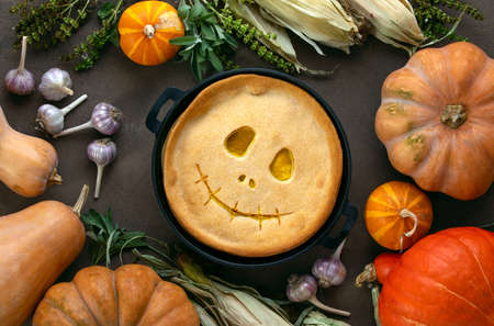 Halloween kids party pumpkin pie baking concept, top down view on a cute skillet baked pumpkin pie with smiling alike Jack-o-lantern face