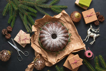 Christmas gifts packing concept, view from above on home baked plain bundt cake to be packed for sweet simple present during Xmas winter holidays