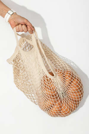Hand is holding a pumpkin in a shopping bag, autumn shopping sale concept 写真素材