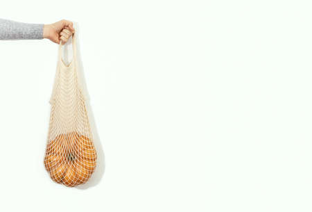 Hand is holding a pumpkin in a shopping bag, front view, autumn sale concept, copy space for a text 写真素材